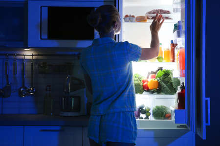 Woman choosing food from refrigerator in kitchen at night 免版税图像