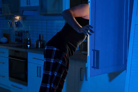 Man looking into refrigerator and choosing products in kitchen at night