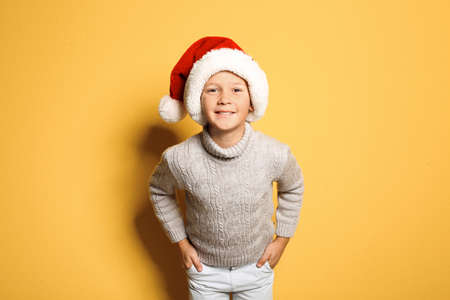 Cute little boy in warm sweater and Christmas hat on color background