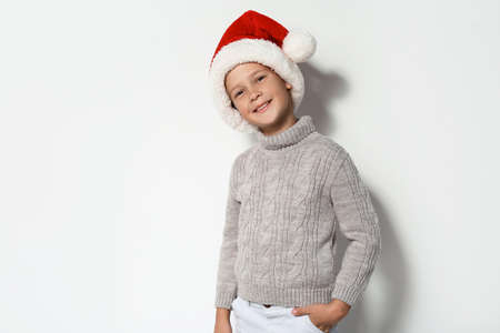 Cute little boy in warm sweater and Christmas hat on white background