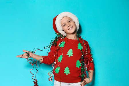 Netter kleiner Junge in handgemachtem Weihnachtspullover und Hut mit Luftschlangen auf farbigem Hintergrund Standard-Bild