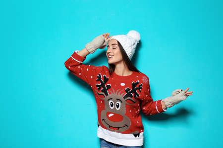 Junge Frau in Weihnachtspullover und Strickmütze auf farbigem Hintergrund