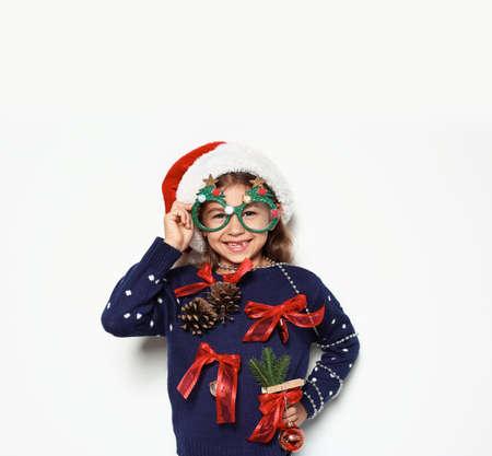 Nettes kleines Mädchen in handgemachtem Weihnachtspullover und Hut mit Partybrille auf weißem Hintergrund