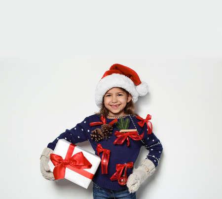Nettes kleines Mädchen in handgemachter Weihnachtsstrickjacke und -mütze mit Geschenk auf weißem Hintergrund Standard-Bild