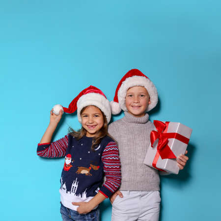 Cute children in warm sweaters and Christmas hats and gift on color background