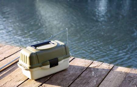 Tackle Box und Rute zum Angeln auf Holzsteg am Flussufer. Freizeitgestaltung