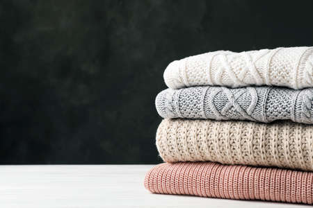 Stack of folded knitted sweaters on table. Space for text