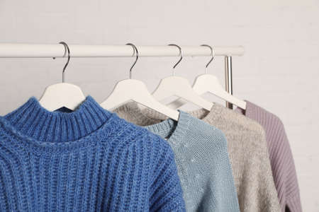 Collection of warm sweaters hanging on rack against white background, closeup Stock Photo
