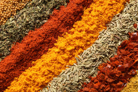Rows of different aromatic spices as background, top view