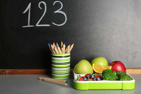 Healthy food for school child in lunch box and stationery on table near blackboard with chalk written numbers Banco de Imagens