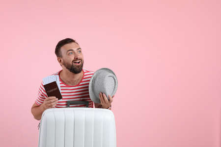 Man with suitcase, passport and hat on color background. Space for text Stock fotó - 115399231