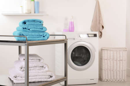 Stacked clean soft towels on table in laundry room. Space for text Stock Photo