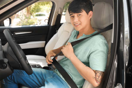 Male driver fastening safety belt in car 版權商用圖片