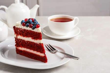 Plate with piece of delicious homemade red velvet cake on table. Space for text