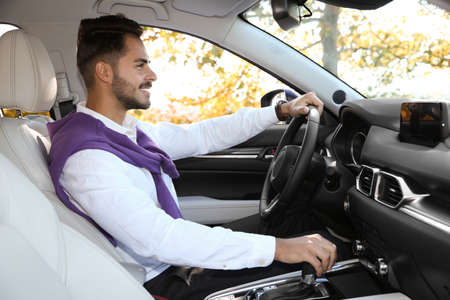 Young man in driver's seat of modern car Stock Photo