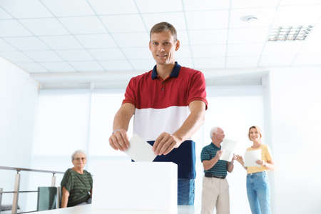 Man putting ballot paper into box at polling station