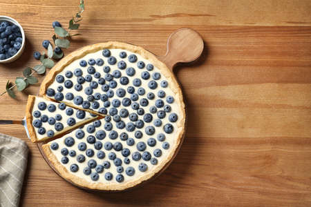 Flat lay composition with tasty blueberry cake and space for text on wooden table Stock Photo