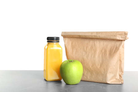 Healthy food and paper bag on table against white background. School lunch