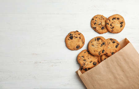 Paper bag with delicious chocolate chip cookies on wooden table, flat lay. Space for text Stock Photo