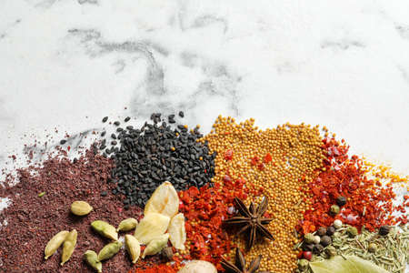 Different aromatic spices on marble background, top view with space for text
