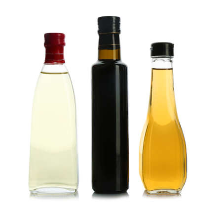 Glass bottles with different kinds of vinegar on white background Stock Photo
