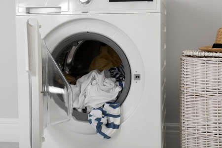 Washing machine with laundry near wall in room