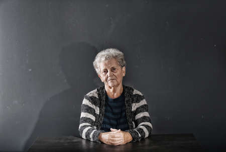Portrait of poor elderly woman sitting at table on dark background