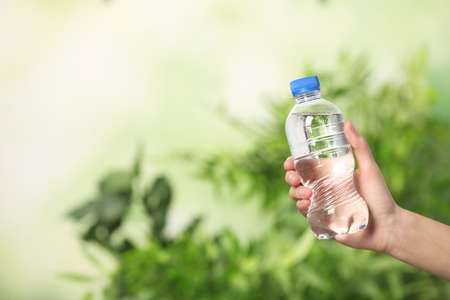 Woman holding bottle of water on blurred background. Space for text