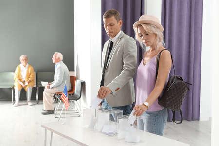 Personas poniendo papeletas en urnas en el colegio electoral