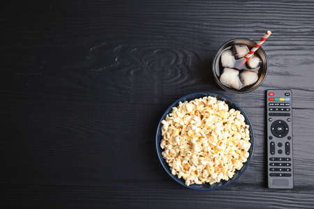 Bowl with popcorn, glass of iced cola and TV remote on wooden background, top view with space for text. Watching cinema Stock Photo