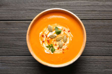 Bowl with tasty pumpkin soup on wooden table, top view