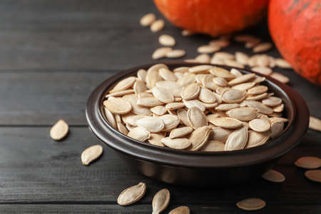 Full bowl of raw pumpkin seeds on wooden table Stock Photo