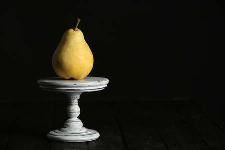 Stand with fresh ripe pear on table against dark background. Space for text Stock Photo