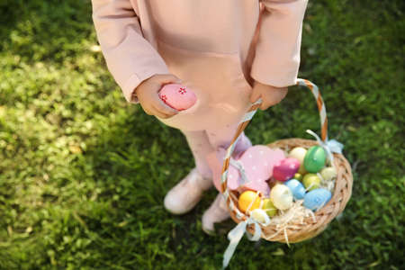 Little girl with basket of Easter eggs in park, closeup