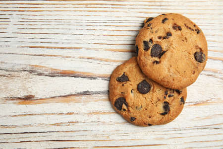 Delicious chocolate chip cookies on wooden table, flat lay.