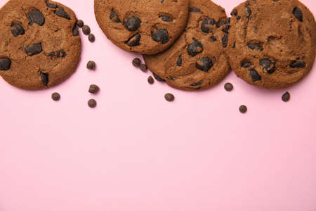 Delicious chocolate chip cookies on color background, flat lay.