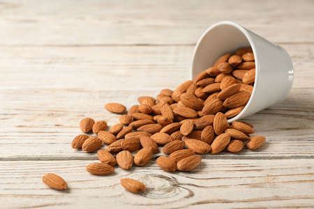 Tasty organic almond nuts and bowl on table