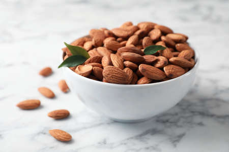 Tasty organic almond nuts in bowl on table Stock Photo