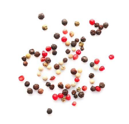Mix of different pepper grains on white background, top view