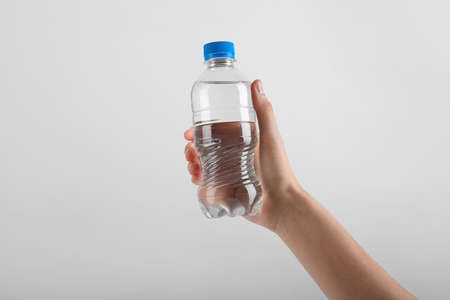 Woman holding plastic bottle with water on white background