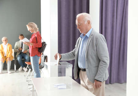 Elderly man putting ballot paper into box at polling station
