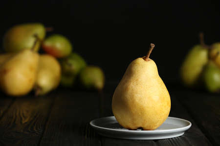 Plate with fresh ripe pear on table against blurred background Stock Photo