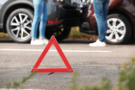 Emergency stop sign near people discussing car accident on road. Auto insurance