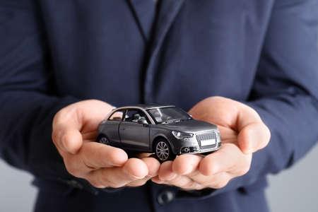 Mężczyzna agent ubezpieczeniowy posiadający samochodzik na szarym tle, zbliżenie