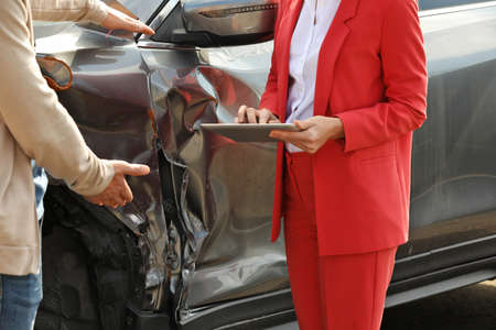Man reporting and insurance agent with tablet filling claim form near broken car after accident