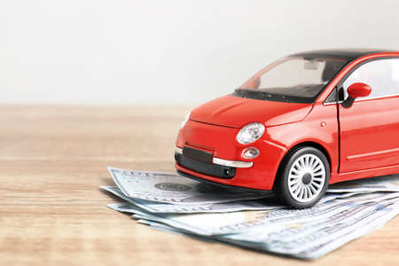 Toy car and money on table, space for text. Vehicle insurance