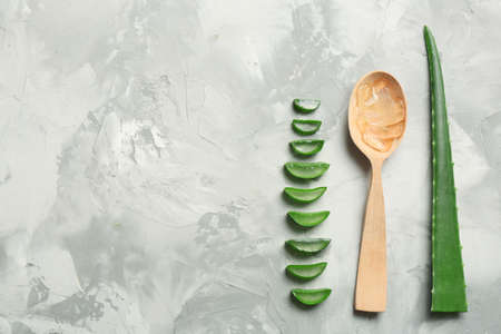 Flat lay composition with aloe vera leaves and space for text on gray background