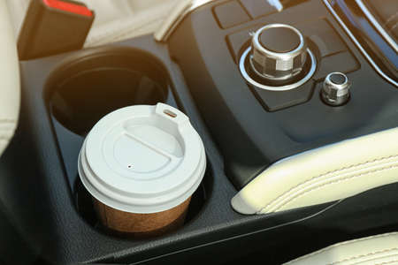 Takeaway paper coffee cup in holder inside car