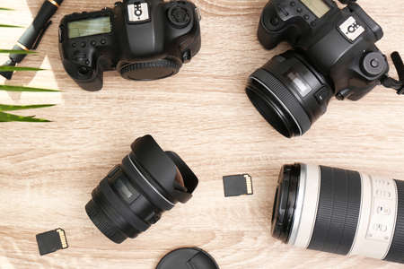 Professional photographers equipment on wooden table, top view