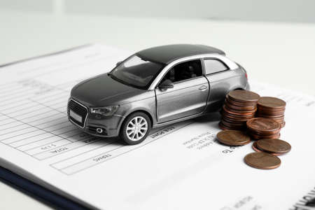 Toy car, money and insurance contract on table